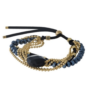 Black faux suede, pull-tie bracelet featuring hematite beads, a black natural stone, and gold tone accents.