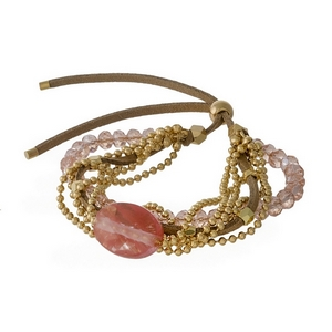 Tan faux suede, pull-tie bracelet featuring pink beads, a rose cherry quartz natural stone, and gold tone accents.