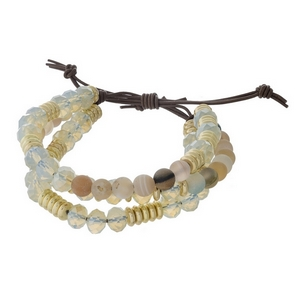 Three row, beaded pull-tie bracelet featuring botswana and opal beads with gold tone accents. Handmade in the USA.