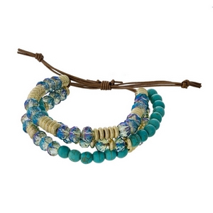 Three row, beaded pull-tie bracelet featuring turquoise and blue iridescent beads with gold tone accents. Handmade in the USA.