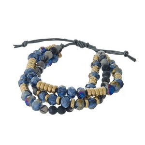 Three row, beaded pull-tie bracelet featuring gray jasper and navy blue beads with gold tone accents. Handmade in the USA.