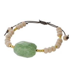 Ivory and gold tone beaded pull-tie bracelet featuring a natural stone focal. Handmade in the USA.