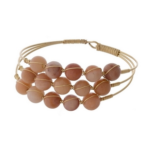 Gold tone bracelet featuring three rows of wire wrapped peach natural stone beads.