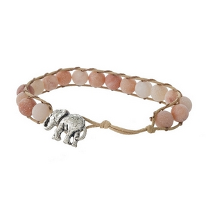 Tan cord bracelet featuring peach natural stone beads and a silver tone elephant toggle closure.