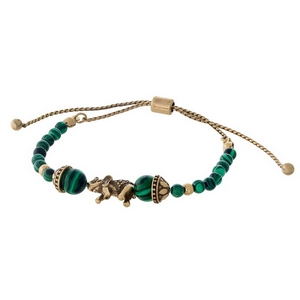 Green beaded pull-tie bracelet with a gold tone elephant focal.