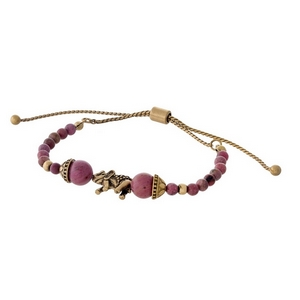 Mauve beaded pull-tie bracelet with a gold tone elephant focal.