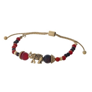 Red beaded pull-tie bracelet with a gold tone elephant focal.