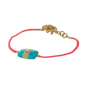 Neon pink braided cord toggle bracelet with a turquoise stone focal and gold tone accents.