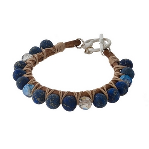Brown leather toggle bracelet featuring wrapped sodalite natural stone beads and gold tone accents.