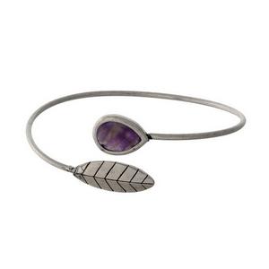 Silver tone cuff bracelet with a leaf and a purple stone.