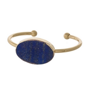 Gold tone cuff bracelet with a lapis natural stone focal.
