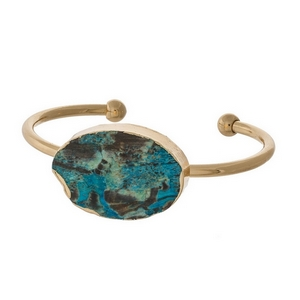 Gold tone cuff bracelet with a turquoise natural stone focal. Each stone varies in color and shape.