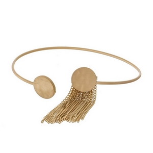 Dainty gold tone cuff bracelet with a chain tassel accent.