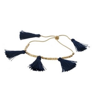 Dainty gold tone pull-tie bracelet with navy blue thread tassels.