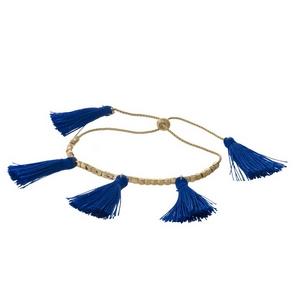 Dainty gold tone pull-tie bracelet with royal blue thread tassels.