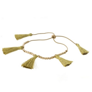Dainty gold tone pull-tie bracelet with gold thread tassels.