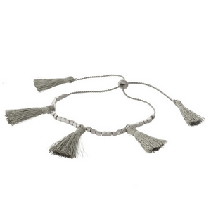 Dainty silver tone pull-tie bracelet with silver thread tassels.