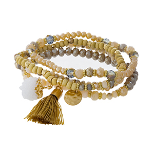 Champagne, ivory and gold tone beaded four piece bracelet set with a tassel accent.