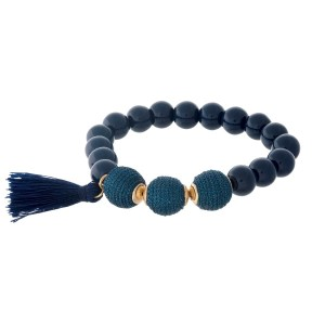Navy blue beaded stretch bracelet with thread wrapped beads and a tassel accent.