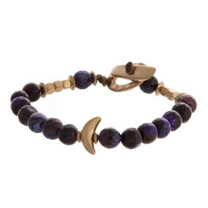 Natural stone beaded stretch bracelet with gold tone accents and a toggle closure.