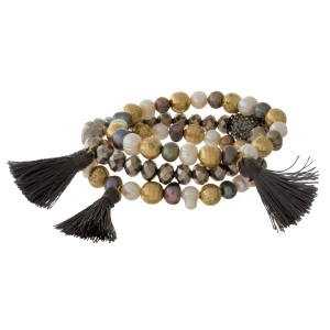 Three piece beaded stretch bracelet with gold tone accents, freshwater pearl beads, and a tassel accents.
