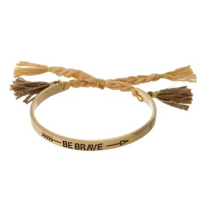 "Gold tone bangle bracelet stamped with ""Be Brave"" and a pull-tie closure."