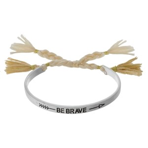 "Silver tone bangle bracelet stamped with ""Be Brave"" and a pull-tie closure."