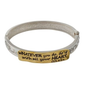 Silver tone bangle bracelet with a two tone focal stamped with Colossians 3:23 and a hinge closure.