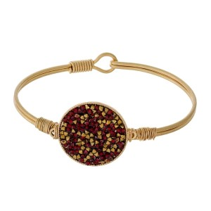 Gold tone, metal bangle bracelet with a crushed rhinestone circle focal.