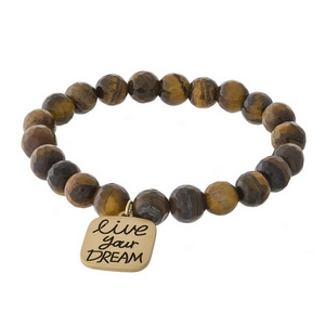 "Beaded stretch bracelet with a gold tone charm stamped with ""live your dream."""