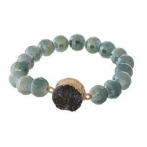 Beaded stretch bracelet with a natural, druzy stone focal and gold tone accents.