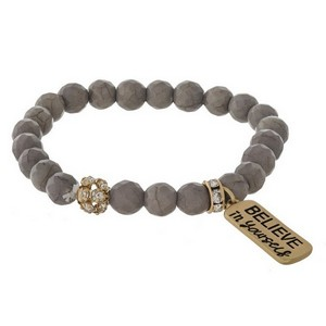 "Beaded stretch bracelet with a gold tone charm stamped with ""Believe in Yourself."""