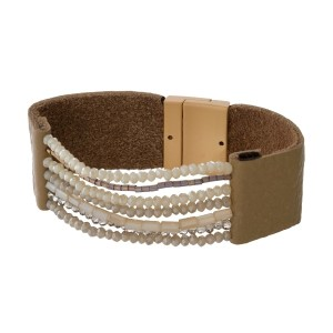 Genuine leather bracelet with monochromatic beads and a gold tone magnetic closure.