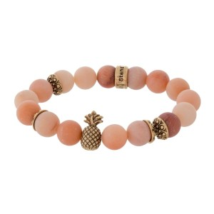 Natural stone beaded stretch bracelet with a gold tone pineapple accent.