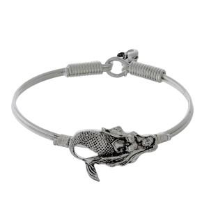 Silver tone bangle bracelet with a sea life focal and a hook closure.