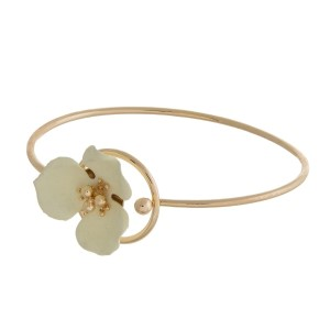 Dainty gold tone bangle bracelet with a flower focal.