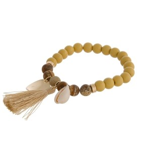 Natural stone and freshwater pearl beaded stretch bracelet with a shell and tassel charm.
