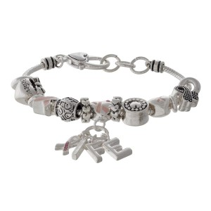 Metal bracelet with breast cancer awareness ribbon.
