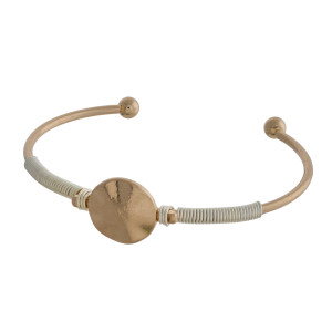 Metal cuff bracelet with wire wrap detail and circle focal.