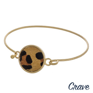 "Gold metal bangle bracelet featuring a leopard print faux leather focal. Approximately 2.5"" in diameter. Fits up to a 5"" wrist."
