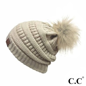 Cable knit, original C.C beanie with a faux fur pom pom, in beige. 100% acrylic.