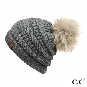Cable knit, original C.C beanie with a faux fur pom pom, in light melange gray. 100% acrylic.