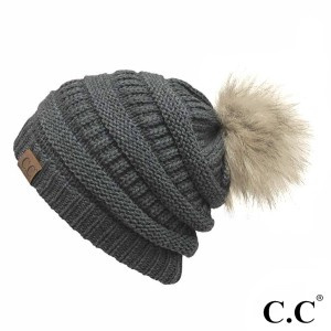 Cable knit, original C.C beanie with a faux fur pom pom, in dark melange gray. 100% acrylic.