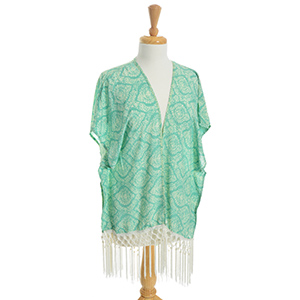 Lightweight green kimono top with ivory paisley print and fringe decor. 100% Viscose. One size fits most.