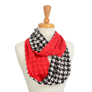 Lightweight infinity scarf with a black and white houndstooth print and crimson lining. Polyester and viscose blend.