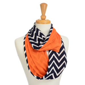 Lightweight infinity scarf featuring a navy blue and white chevron pattern with an orange lining. Polyester and viscose blend.