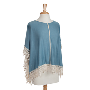 Blue knit poncho top with ivory lace trim. 25% Polyester and 75% viscose. One size fits most.