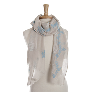 Beige open scarf with sky blue and white embroidered flowers. 65% polyester and 35% viscose.