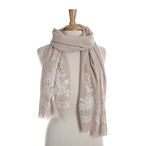 Beige open scarf with white floral embroidery details. 65% polyester and 35% viscose.