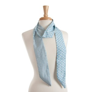 "Reversible light blue skinny scarf with white polka dots on one side and white stripes on the other. Can also be worn as a headband. 100% polyester. Approx. 68"" x 2.5"""